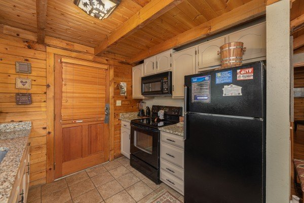 Galley kitchen with black appliances at Snuggle Inn, a 2 bedroom cabin rental located in Pigeon Forge