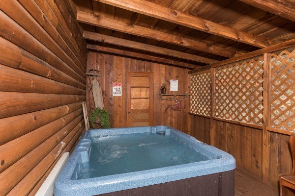 Hot tub on a covered porch with privacy lattice at Snuggle Inn, a 2 bedroom cabin rental located in Pigeon Forge
