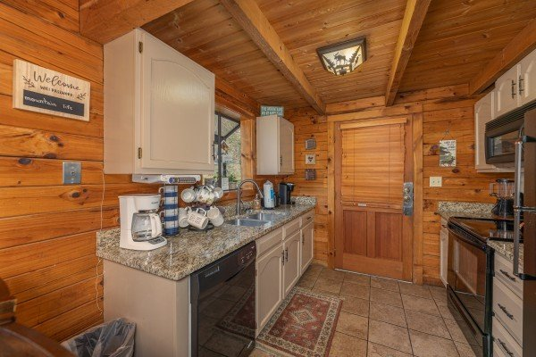 Kitchen with black appliances at Snuggle Inn, a 2 bedroom cabin rental located in Pigeon Forge
