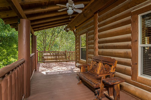 Covered porch with a gliding bench and a swing at Longwalker Lodge, a 3 bedroom cabin rental located in Pigeon Forge