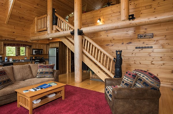 Open concept main floor with custom beams and bear wood carvings at Longwalker Lodge, a 3 bedroom cabin rental located in Pigeon Forge