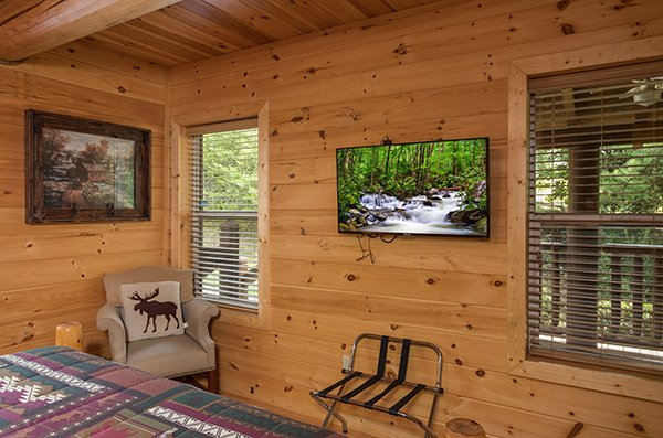 Bedroom with a suitcase stand, chair, and TV at Longwalker Lodge, a 3 bedroom cabin rental located in Pigeon Forge