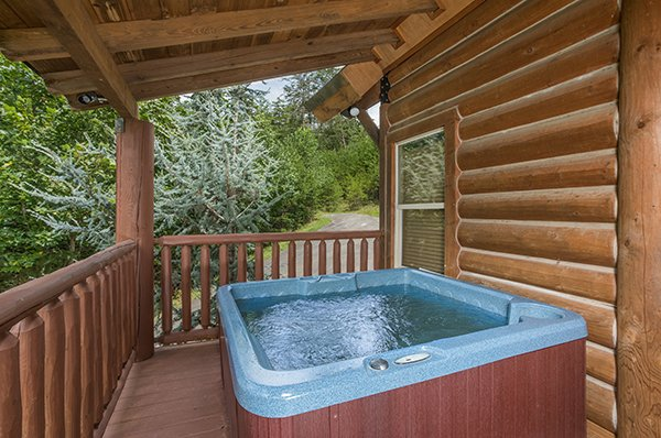 Hot tub on a covered deck at Longwalker Lodge, a 3 bedroom cabin rental located in Pigeon Forge