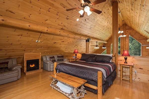 King-sized bed in the loft space near a fireplace at Longwalker Lodge, a 3 bedroom cabin rental located in Pigeon Forge