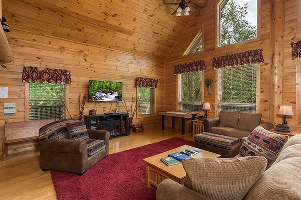 Living room with a television, vaulted ceiling, and large windows at Longwalker Lodge, a 3 bedroom cabin rental located in Pigeon Forge