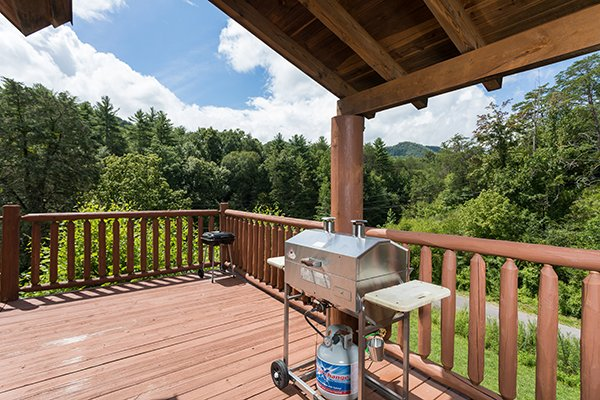Propane grill on a covered deck at Longwalker Lodge, a 3 bedroom cabin rental located in Pigeon Forge