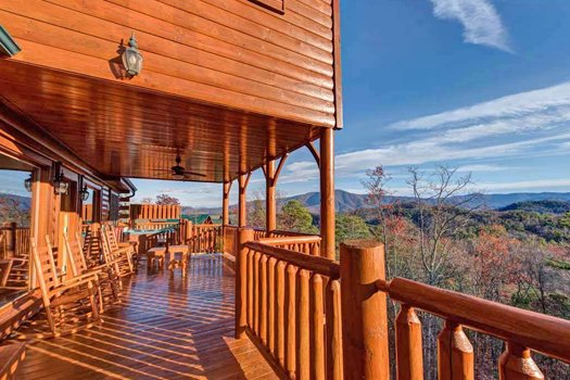 Looking across the large deck across to the Smoky Mountain Views at Grand Timber Lodge, a 5-bedroom cabin rental located in Pigeon Forge