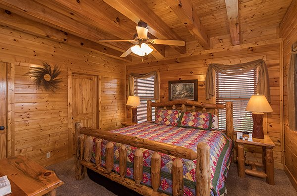 King-sized log bed at Grand Timber Lodge, a 5-bedroom cabin rental located in Pigeon Forge