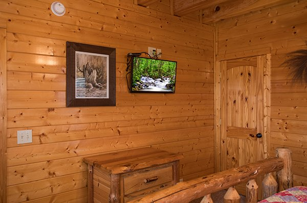 Bedroom with a night stand and a TV at Grand Timber Lodge, a 5-bedroom cabin rental located in Pigeon Forge