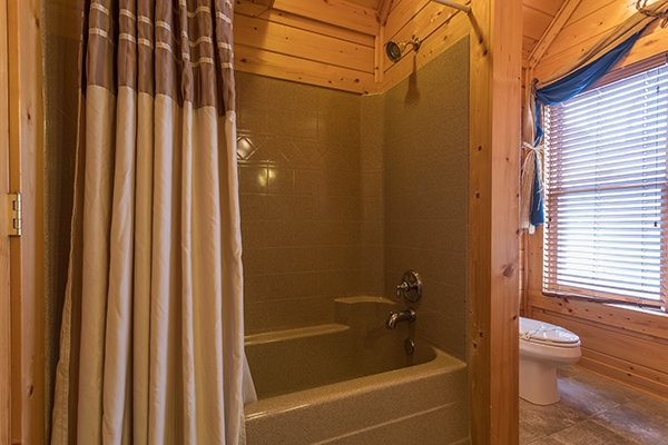 Upstairs bathroom with a tub and shower at Grand Timber Lodge, a 5-bedroom cabin rental located in Pigeon Forge