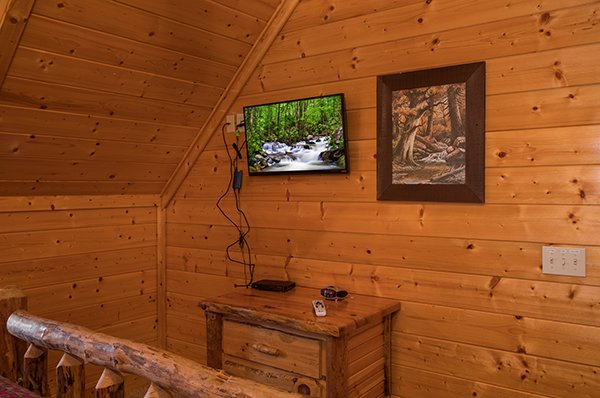 Bedroom with a side table and television at Grand Timber Lodge, a 5-bedroom cabin rental located in Pigeon Forge