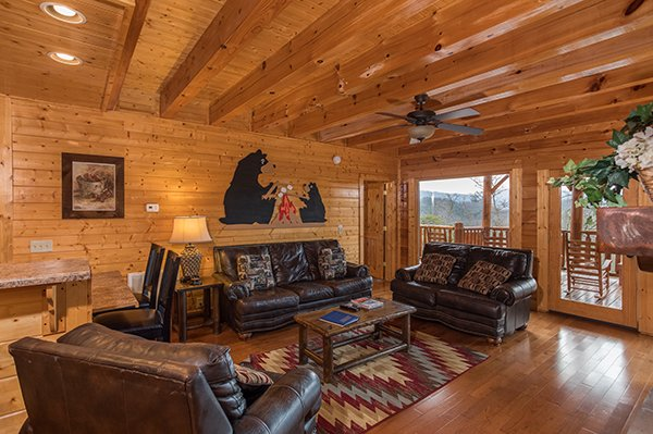 Living room with sleeper sofa and deck access at Grand Timber Lodge, a 5-bedroom cabin rental located in Pigeon Forge