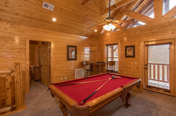 Red felted pool table in the loft space at Grand Timber Lodge, a 5-bedroom cabin rental located in Pigeon Forge