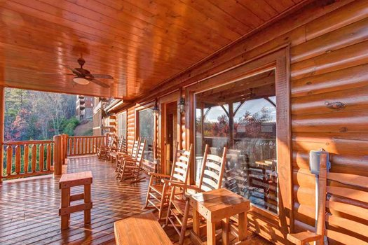 Rocking chairs on a covered deck overlooking the Smokies at Grand Timber Lodge, a 5-bedroom cabin rental located in Pigeon Forge