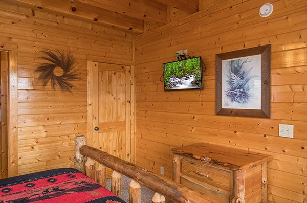 Bedroom with a TV and nightstand at Grand Timber Lodge, a 5-bedroom cabin rental located in Pigeon Forge