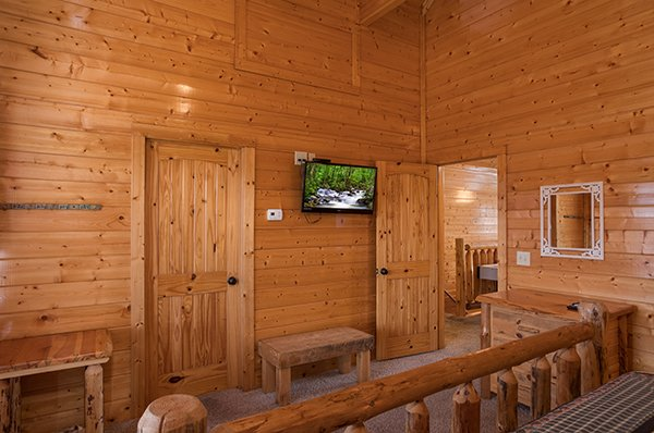 Bedroom with a bench, table, dresser, and TV at Grand Timber Lodge, a 5-bedroom cabin rental located in Pigeon Forge