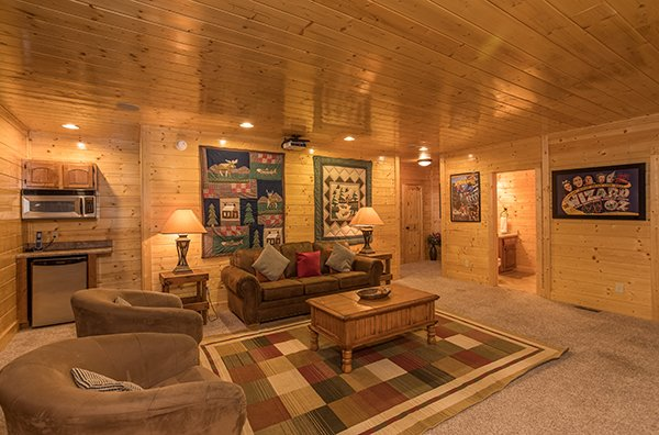 Sleeper sofa, two chairs, a mini fridge, and a microwave in the theater room at Grand Timber Lodge, a 5-bedroom cabin rental located in Pigeon Forge