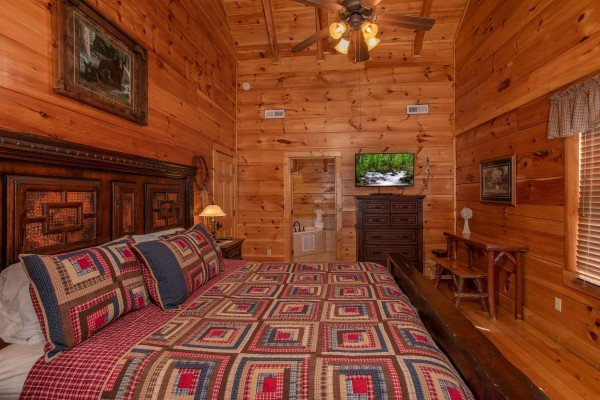 Bedroom with a king-sized bed, dresser, writing desk, and television at Bearfoot Paradise, a 3-bedroom cabin rental located in Pigeon Forge