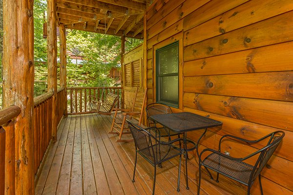 Deck with a bistro set for three, porch swing and rocking chair at Bearfoot Paradise, a 3-bedroom cabin rental located in Pigeon Forge