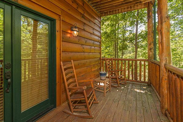 Deck with two rocking chairs and a small table at Bearfoot Paradise, a 3-bedroom cabin rental located in Pigeon Forge