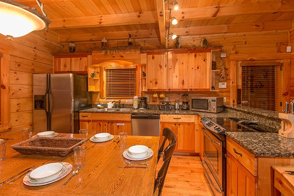 Dining table in the kitchen with stainless steel appliances at Bearfoot Paradise, a 3-bedroom cabin rental located in Pigeon Forge