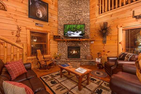 Living room with stacked stone fireplace and television at Bearfoot Paradise, a 3-bedroom cabin rental located in Pigeon Forge