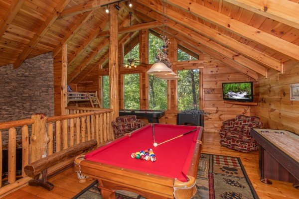 Red felted pool table in the game loft at Bearfoot Paradise, a 3-bedroom cabin rental located in Pigeon Forge