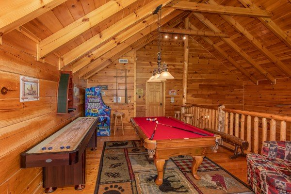 Shuffleboard and pool tables in the game loft at Bearfoot Paradise, a 3-bedroom cabin rental located in Pigeon Forge