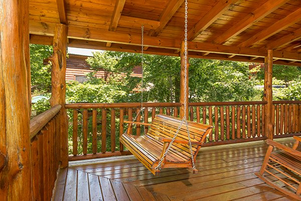 Swing on a covered porch at Bearfoot Paradise, a 3-bedroom cabin rental located in Pigeon Forge