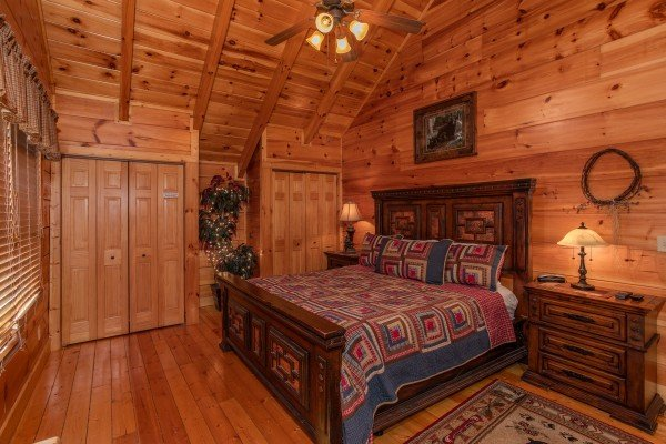 Bedroom with a king-sized wooden bed at Bearfoot Paradise, a 3-bedroom cabin rental located in Pigeon Forge