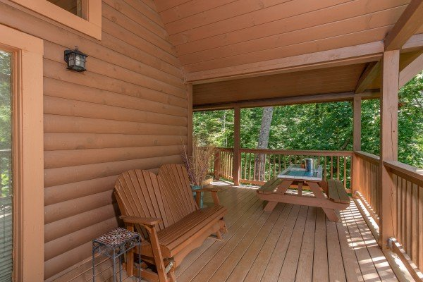 adirondak bench and picnic table on a covered deck at almost heaven a 1 bedroom cabin rental located in pigeon forge