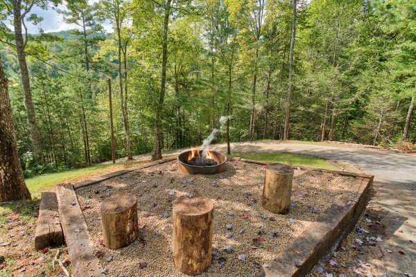 fire pit with log seating at almost heaven a 1 bedroom cabin rental located in pigeon forge