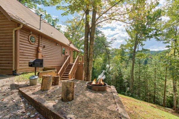fire pit with log seating and charcoal grill at almost heaven a 1 bedroom cabin rental located in pigeon forge
