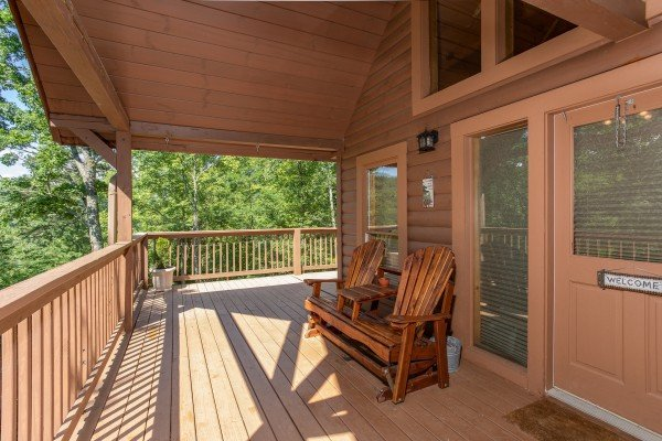 front porch with adirondak bench seating at almost heaven a 1 bedroom cabin rental located in pigeon forge