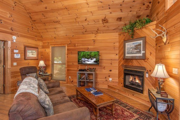 living room with couch television and fireplace at almost heaven a 1 bedroom cabin rental located in pigeon forge