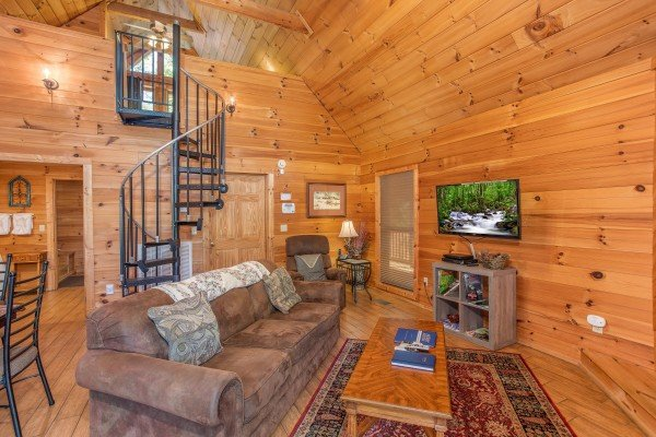 living room with a spiral staircase at almost heaven a 1 bedroom cabin rental located in pigeon forge