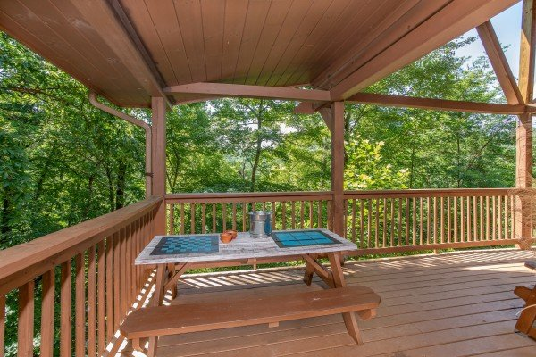 picnic table with games on a covered deck at almost heaven a 1 bedroom cabin rental located in pigeon forge