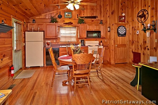 dining table with seating for four and the kitchen at always together forever a 1 bedroom cabin rental located in pigeon forge