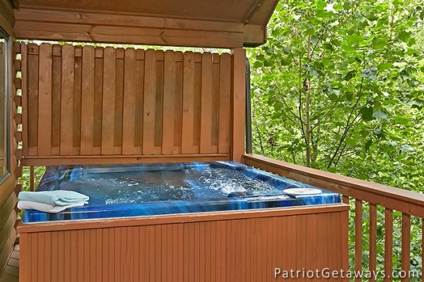 hot tub on a covered porch with privacy fence at always together forever a 1 bedroom cabin rental located in pigeon forge