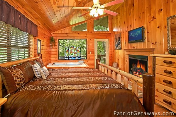 king sized log bed with fireplace and jacuzzi at always together forever a 1 bedroom cabin rental located in pigeon forge