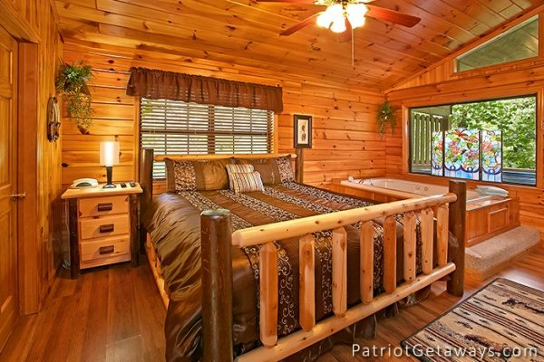 king sized log bed next to a jacuzzi at always together forever a 1 bedroom cabin rental located in pigeon forge