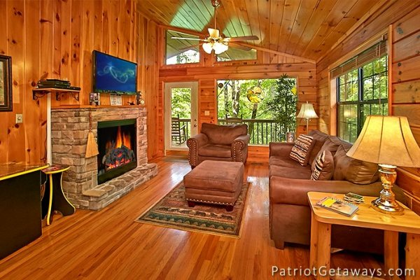 living room with a sofa large chair stone fireplace and television at always together forever a 1 bedroom cabin rental located in pigeon forge