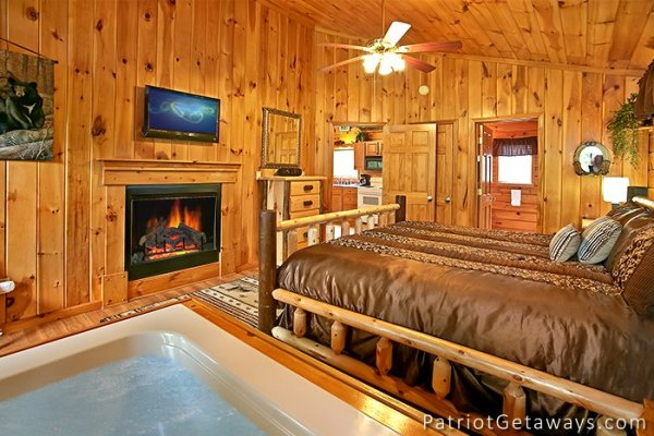 master bedroom with fireplace and jacuzzi at always together forever a 1 bedroom cabin rental located in pigeon forge