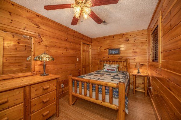 Bedroom with a bed, night stand, lamps, and dresser at Pine Splendor, a 5 bedroom cabin rental located in Pigeon Forge
