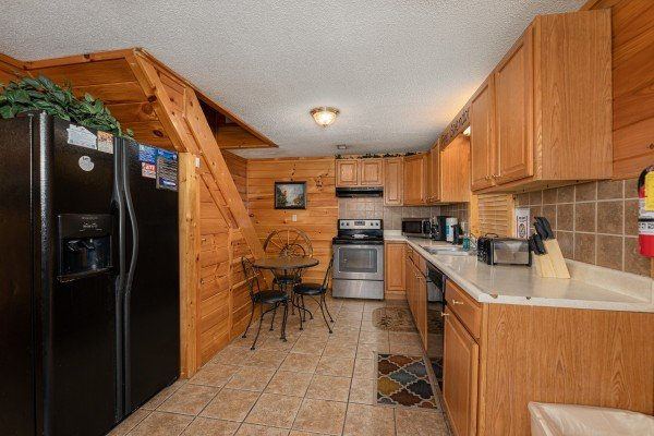 Kitchen with black and stainless appliances at Pine Splendor, a 5 bedroom cabin rental located in Pigeon Forge