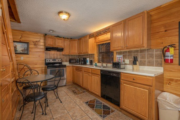 Kitchen with a small bistro set at Pine Splendor, a 5 bedroom cabin rental located in Pigeon Forge