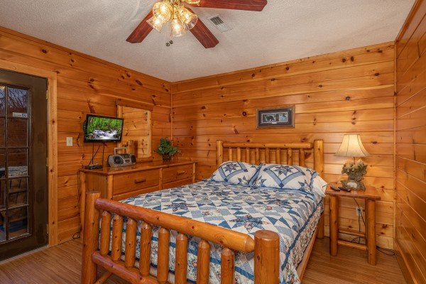 Log bed, dresser, TV, and nightstand in a bedroom at Pine Splendor, a 5 bedroom cabin rental located in Pigeon Forge