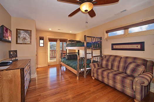 twin over full bunk beds next to sofa in first floor bedroom at horse'n around a 3 bedroom cabin rental located in pigeon forge