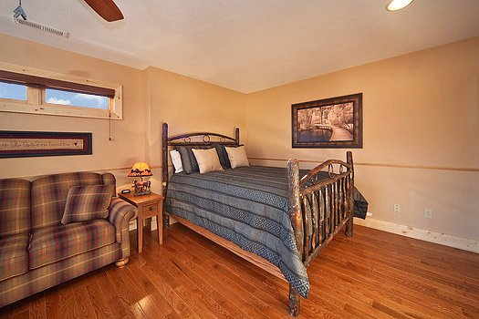 first floor bedroom with queen bed next to a sofa at horse'n around a 3 bedroom cabin rental located in pigeon forge