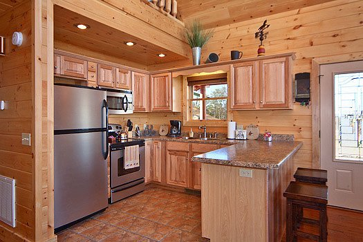 kitchen with stainless appliances and breakfast bar at horse'n around a 3 bedroom cabin rental located in pigeon forge